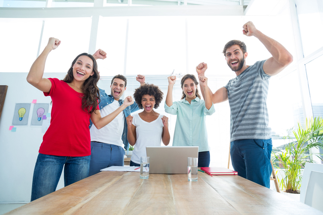 Happy business team with fists in the air at office